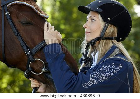 Pretty female rider caressing horse forehead with love.