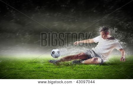 football player in white shirt striking the ball at the stadium under the rain