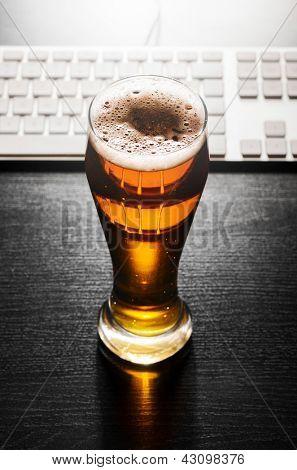 copo de cerveja lager fresca com teclado na mesa preto
