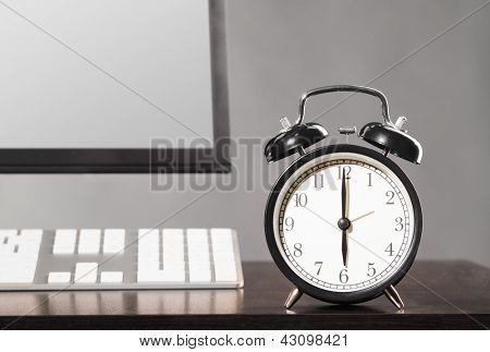 end of working day. office computer with clock on gray background