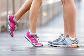 Love sport concept - running couple kissing. Closeup of running shoes and girl standing on toes to k