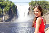 Chute montmorency falls quebec and woman tourist smiling happy in red summer dress looking at