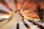 image of repentance  - hands praying with a dramatic red sky overa small town - JPG