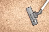 stock photo of suction  - Head of a modern vacuum cleaner on a beige carpet - JPG