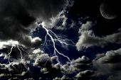 stock photo of bolts  - Several bolts of lightning in night sky with moon in the clouds - JPG