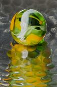 image of dimples  - A green and yellow swirl marble on reflective dimpled metal - JPG