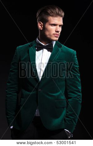 side view of a young elegant man in green velvet suit , he looks away from the camera and stands with hands in pockets