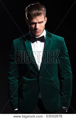 relaxed youn man in green velvet suit is standing with hands in pockets on black background