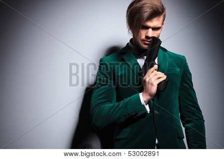 young elegant hitman  waiting in green velvet suit with neck bow