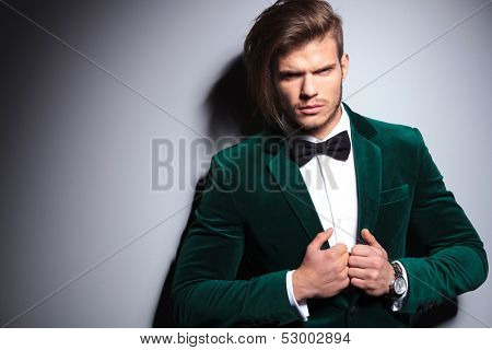 angry young man in green velvet suit looks at the camera on gray background