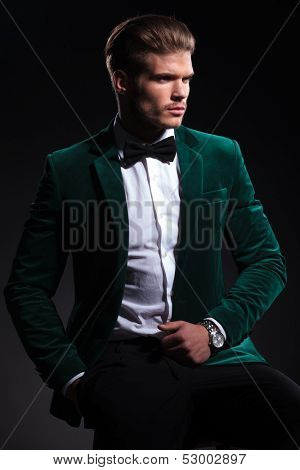 side view of a seated elegant man in green velvet suit, he looks away from the camera on black background