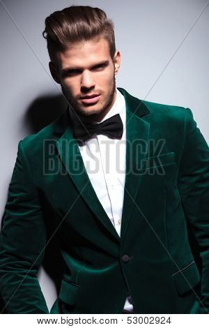 portrait of a happy young man wearing a green velvet suit on gray background