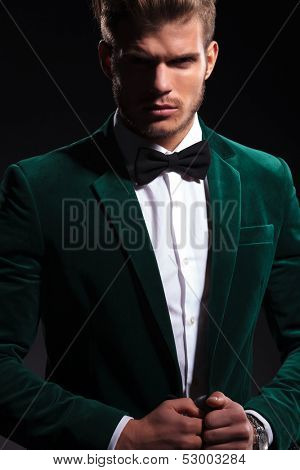 elegant fashion man in velvet suit and neck bow looking at the camera while posing on black background
