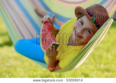 Summer joy - lovely girl eating fresh watermelon in colorful hammock