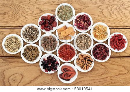 Chinese herbal medicine selection in white porcelain dishes over oak background.