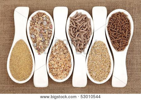 Healthy breakfast cereal selection in white porcelain scoops over hessian background.