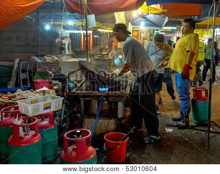 AMPANG - OCTOBER 9: Vendors selling roasted chest-nuts prepare the nuts for sale at the Kau Ong Yah Temple in Ampang, Malaysia during the Nine Emperor Gods festival on October 9, 2013.