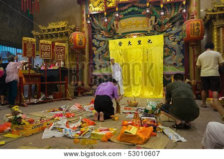 AMPANG - OCTOBER 9: Devotees of the Buddhism-Taosim faith give offerings and pray at the Kau Ong Yah Temple in Ampang, Malaysia at the Nine Emperor Gods festival on October 9, 2013.