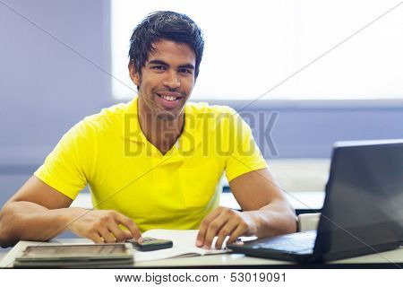 cheerful male indian college student in lecture room