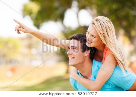 cheerful young couple piggyback and pointing outdoors