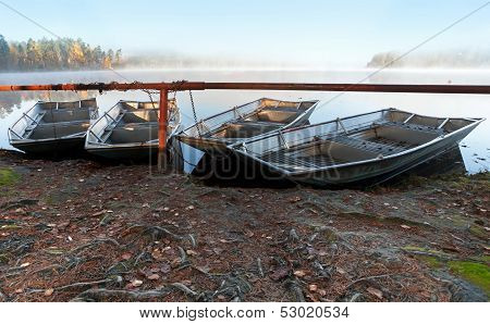 Four Small Metal Rowboats On Still Foggy Lake Coast In The Morning