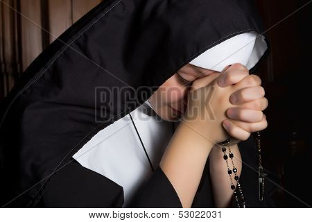 Novice nun praying a rosary in deep prayer with eyes closed
