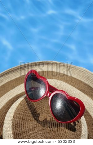 Red Sunglasses And Hat By A Blue Pool