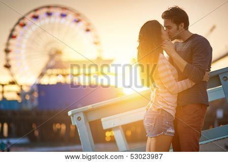 romantic couple kissing at sunset in front of santa monica ferris wheel.