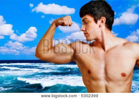 muskuläre Mann zeigt seine Bizeps am Strand
