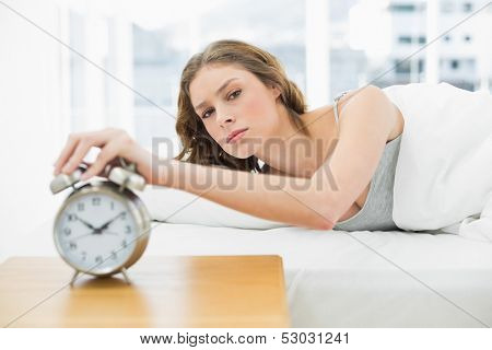 Annoyed beautiful woman turning off the alarm clock while lying in her bed and looking at camera