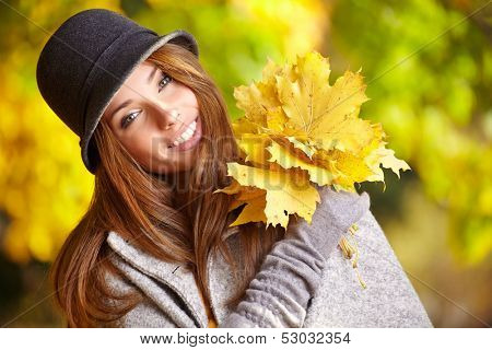 happy fall woman smiling joyful and blissful holding autumn leaves outside in colorful fall forest.