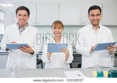 Group of smiling scientists using tablet PCs in the laboratory