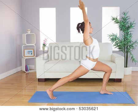 Sporty slim woman practicing yoga pose for stretching her body in her living room