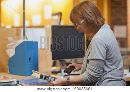Profile view of mature librarian scanning a book behind the desk