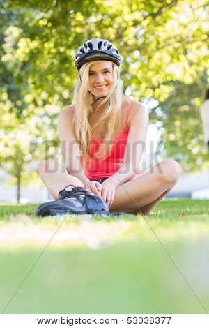 Casual smiling blonde wearing inline skates and helmet sitting in a park