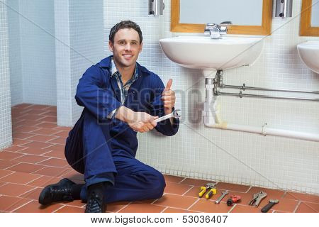 Handsome happy plumber sitting next to sink showing thumb up in public bathroom