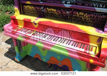 Colorfully decorated old piano stands outside in a park