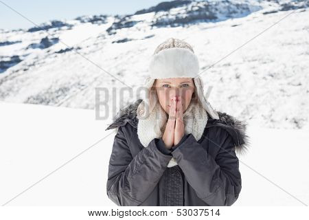 Portrait of a young woman in warm clothing shivering on snow covered landscape