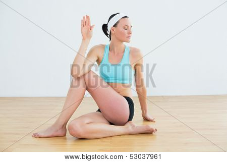 Full length of a fit young woman doing the spine twisting pose at fitness studio