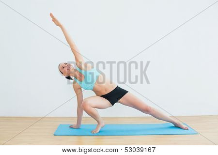 Full length of a slim young woman doing the side plank yoga pose in fitness studio