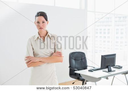 Portrait of an elegant businesswoman standing with arms crossed in office