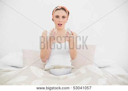 Surprised woman watching television eating popcorn sitting on her bed
