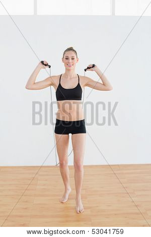Gleeful slender woman holding a rope for skipping looking cheerfully at camera
