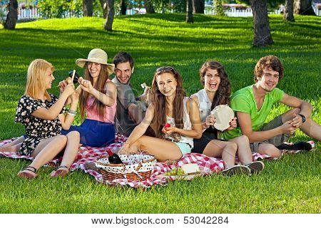 College Students Enjoying A Picnic In The Park