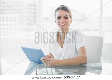 Gleeful smiling businesswoman working with her tablet looking at camera sitting at her desk