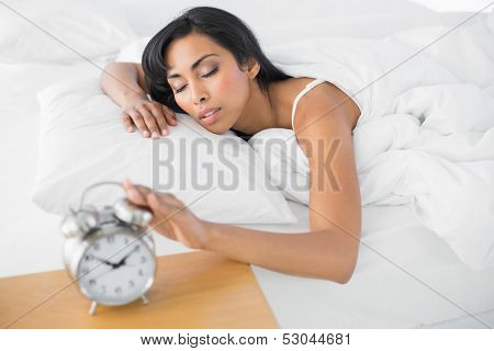 Tired young woman lying in her bed sleeping turning off the retro alarm clock