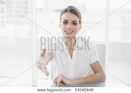 Polite young businesswoman reaching her hand to camera sitting at her desk