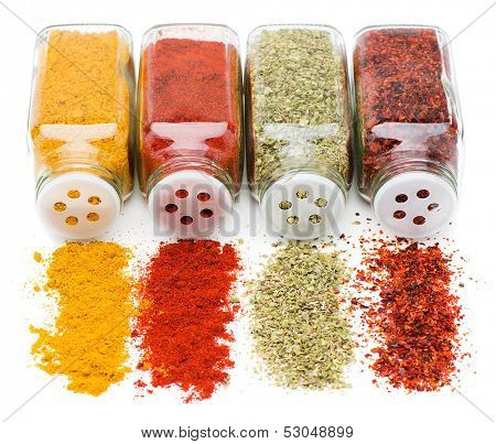 Different spices spilling from spice jars isolated on white background