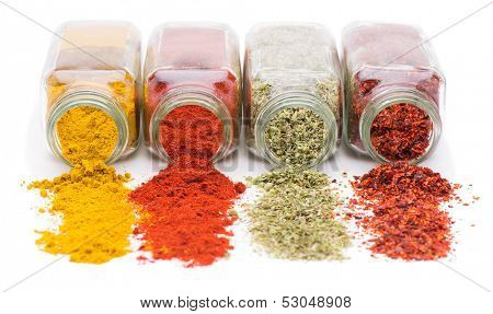Assortment of spices spilling from glass spice jars