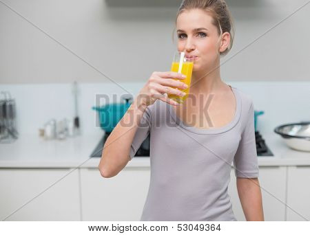 Peaceful gorgeous model looking at camera drinking orange juice standing in kitchen